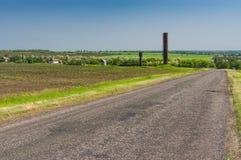 Gestalten Sie mit Landstraße zum ukrainischen entferntdorf an der Frühlings-Saison landschaftlich Lizenzfreie Stockfotografie