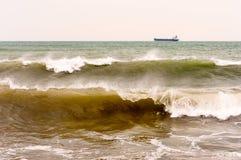 Gestalten Sie mit Meereswellen auf dem Hintergrund landschaftlich, der auf den Straßen des Frachtschiffs steht Stockfotos