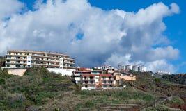 Gestalten Sie mit mehrstöckigen Häusern auf einem Hügel gegen einen Hintergrund des blauen Himmels mit Wolken landschaftlich Stockbild