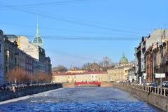 Gestalten Sie mit roter Brücke und Eis über dem Fontanka-Fluss in t landschaftlich Stockfotografie