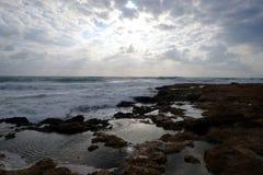 Gestalten Sie mit schönem Sonnenuntergang auf Seeküste mit Steinen im Meer und Wolken auf dem Himmel landschaftlich Lizenzfreies Stockbild