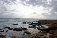 Gestalten Sie mit schönem Sonnenuntergang auf Seeküste mit Steinen im Meer und Wolken auf dem Himmel landschaftlich Stockfotos