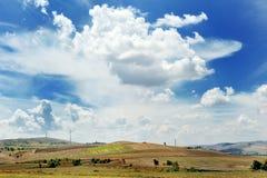 Gestalten Sie mit Turbine des Feldes, des blauen Himmels, der Wolken und der Windenergiegeneratoren landschaftlich Stockbilder