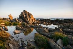 Gestalten Sie am Strand mit der Reflexion der Felsen im Wasser landschaftlich Stockfoto