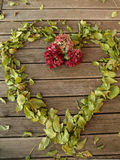 gestalten Sie Whit der alte Bretterboden und Herbstlaub fällt und Blumen Stockbilder