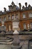 Gestaltete Urnen auf Sockeln vor gewölbter gestalteter Fassade mit Spalten Stockbild