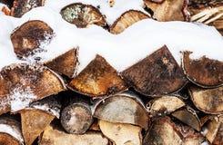 Gestapeld gehakt die brandhout door sneeuw in de winter wordt behandeld Stock Afbeeldingen