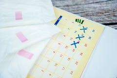 Gestapeld maandverbandstootkussen op kalender royalty-vrije stock afbeeldingen
