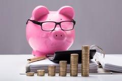 Gestapeld Muntstukken en Document in Front Of Piggy Bank royalty-vrije stock afbeelding