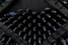 Gestapeld van oude flessen in de kelder stock foto
