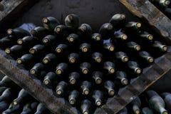 Gestapeld van oude flessen in de kelder Stock Afbeeldingen