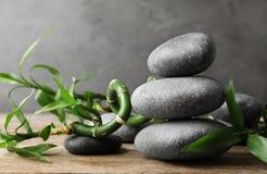 Gestapeld zen stenen en bamboe op lijst tegen grijze achtergrond royalty-vrije stock afbeelding