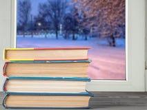 Gestapelde boeken op het bureau tegen het venster stock fotografie