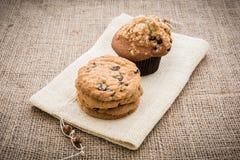 Gestapelde chocoladeschilferkoekjes en cupcakes op bruin servet over Stock Foto
