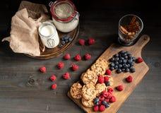Gestapelde de chocoladekoekjes en bessen van de lijstbovenkant naast melk en pijpjes kaneel stock afbeelding