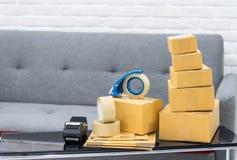 Gestapelde kartonvakjes en hulpmiddelen op lijst met exemplaarruimte stock afbeeldingen