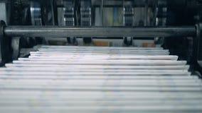 Gestapelde krant op geautomatiseerde transportband, typografiefaciliteit stock video