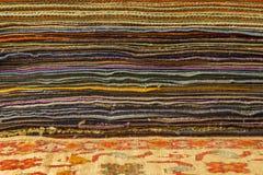 Gestapelde met de hand gemaakte oosterse tapijten en dekens stock foto's