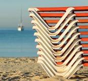 Gestapelde zonbedden op een zandig strand bij zonsopgang Stock Foto