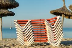 Gestapelde zonbedden op een zandig strand bij zonsopgang Stock Fotografie