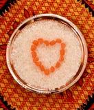Gestapelt in der Herzform-Zuckersüßigkeit beißt auf einer Platte Stockfoto