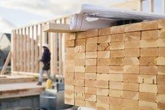 Gestapeltes Bauholz und Lichtpausen an einem Aufbau Si Stockfotografie