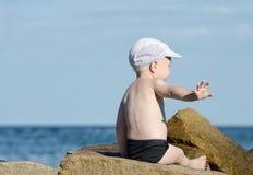 Geste à ne pas tracasser Le petit garçon dans des troncs de natation s'assied sur le bord de la mer, endroit pour le texte Images stock