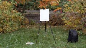 Gestell, schwarzer Rucksack und Farben stehen auf dem Gras im Herbstpark lizenzfreies stockfoto