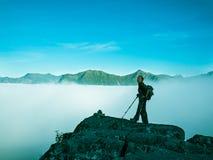 Gestemd beeld van een volwassen vrouw die zich bovenop een berg met een rugzak en Alpenstocks tegen bergen in een mist bevinden Royalty-vrije Stock Foto's