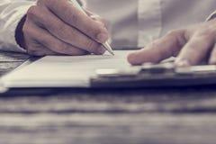 Gestemd beeld van mannelijke hand die bedrijfscontract ondertekenen stock fotografie