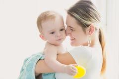 Gestemd portret van gelukkige glimlachende moeder die haar baby na bedelaars houden Royalty-vrije Stock Foto