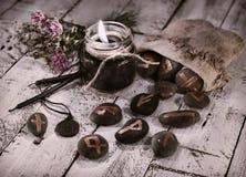 Gestemd stilleven met zwarte kaarsen en runen Stock Foto