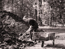Gestemd vuil beeld weinig jongen met een schop in zijn handen die zich naast ijzerkarretje en gravende steenkool tegen de achterg stock foto's