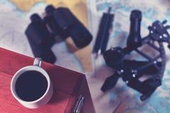 Gestemde achtergrond met kop van koffie en vage navigatieapparatuur Het concept van het overzeese reistoerisme stock afbeeldingen