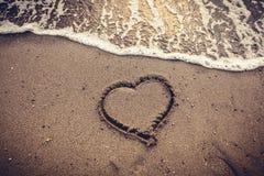 Gestemde die foto van hart op zand overzees strand wordt getrokken Royalty-vrije Stock Afbeeldingen