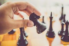Gestemde foto van de mens die beweging met zwart paard maken bij schaakspel Royalty-vrije Stock Afbeelding