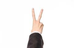 Gesten- und Geschäftsthema: Geschäftsmann zeigt Handzeichen mit einer Erstperson in einem schwarzen Anzug auf einem weißen lokali Lizenzfreies Stockbild