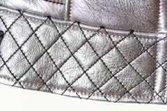 Gesteppter Rand der Torsion mit Nähten in Form eines Gitters, Hintergrund Silberne Farbe von Kleidung Makro Lizenzfreie Stockfotos