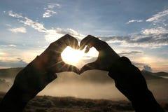 Gestes en forme de coeur dans le paysage de coucher du soleil Photo stock