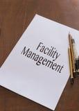 Gestión de instalaciones escrita en el papel Foto de archivo libre de regalías