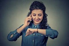 Gestión del negocio y de tiempo Mujer feliz que mira el reloj, corriendo tarde para encontrarse foto de archivo