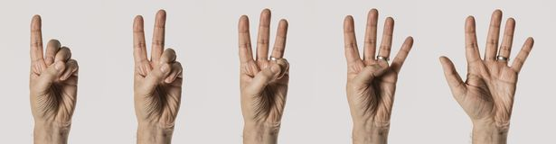 Gesti di mano dell'uomo, contanti i numeri uno - cinque, isolato su fondo bianco immagini stock
