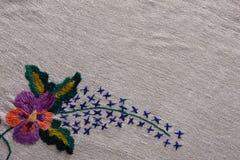 Gestickte Blume auf altem Segeltuchhintergrund Stockfotografie