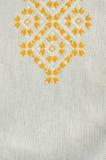 Gesticktes Fragment auf Flachs durch die gelben und weißen Baumwollthreads Flacher Stich der Makrostickereibeschaffenheit lizenzfreie stockbilder