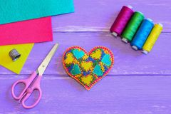 Gesticktes Herz für Valentinsgruß-Tag Angefülltes gesticktes Filzherz, Threadsatz, Scheren, Muffe, bunter Filz bedeckt Stockfoto