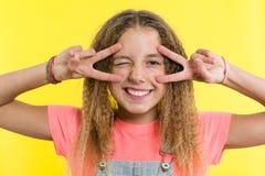 Gesticolare felice dell'adolescente, coprente un occhio, fondo giallo luminoso dello studio Fotografia Stock Libera da Diritti