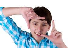 Gesticular el marco del finger Adolescente hermoso que mira la cámara y que gesticula el marco del finger mientras que se coloca  Fotos de archivo
