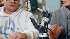 Gesticular robótico do homem Dedos moventes do braço biônico inovativo real vídeos de arquivo