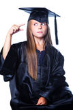 Gesticulating girl in graduation dress on isolated. Portrait of cute girl in black academic cap and gown showing by gesture small or little on isolated white Stock Photos