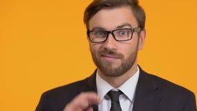 Gesticulation déçue d'homme, recherchant la décision, d'isolement sur le fond orange banque de vidéos